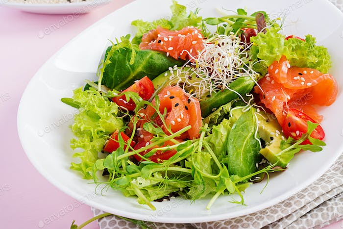 Healthy salad of fresh vegetables - tomatoes, avocado, arugula, seeds and salmon