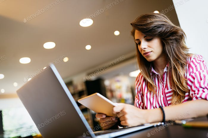 Portrait of happy student woman working on laptop