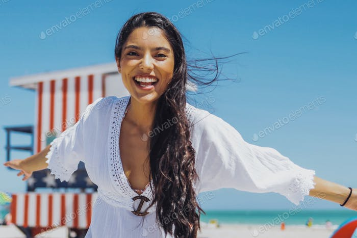 Cheerful ethnic woman laughing on beach