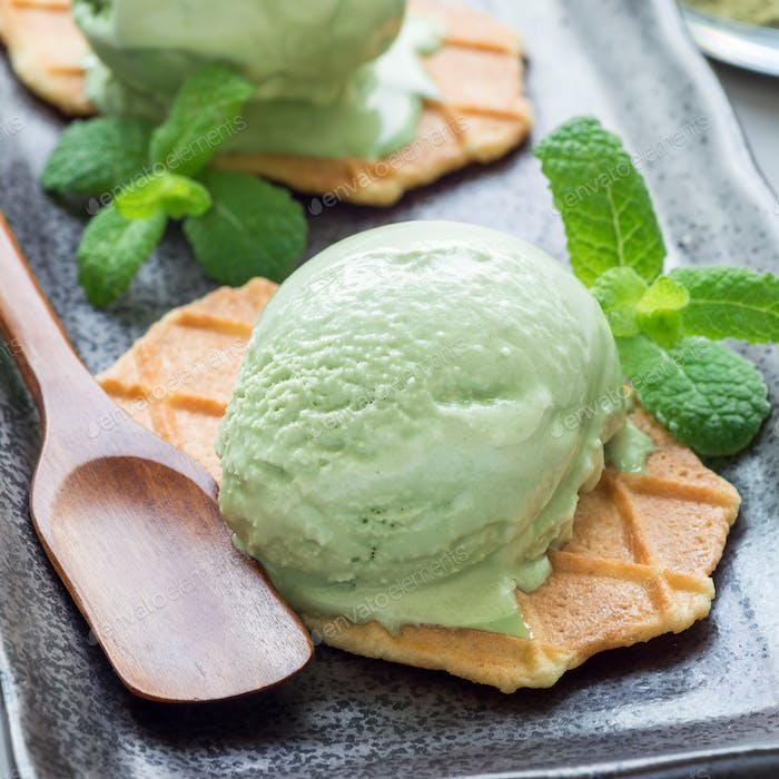 Matcha green tea ice cream balls served with waffles on black plate, square format