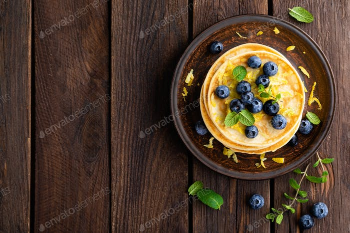 Pancakes with fresh blueberry on wooden rustic background. Top view