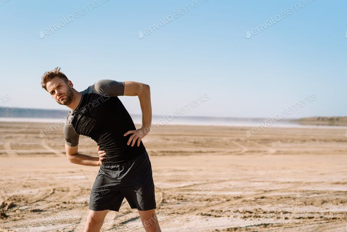 Motivated focused young sportsman exercising