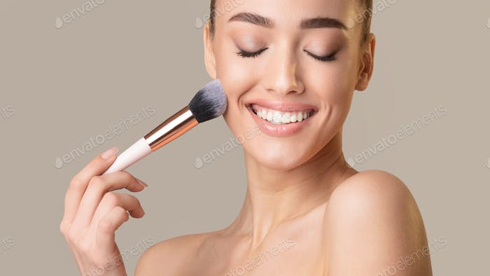 Attractive Woman Applying Face Powder On Beige Studio Background, Panorama
