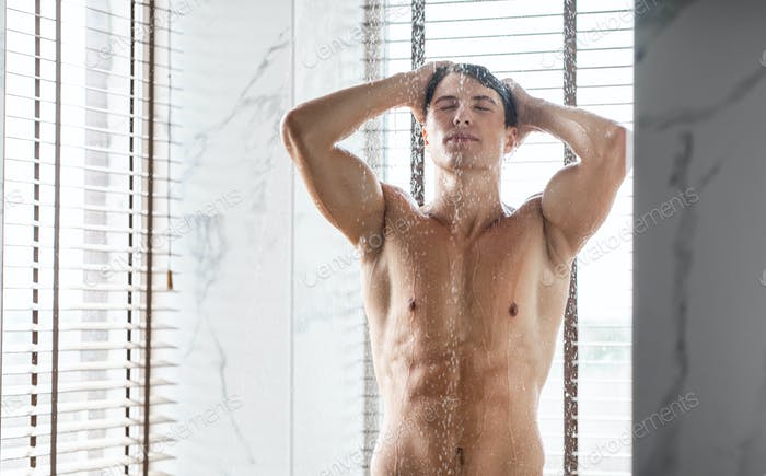 Charming young guy washing hair and body