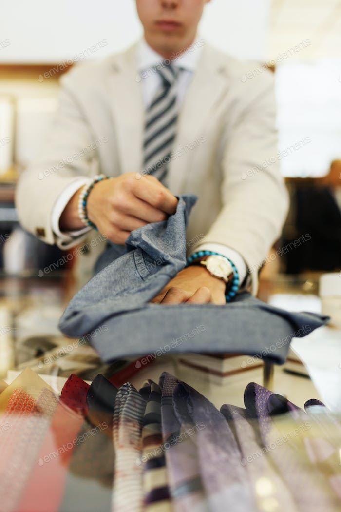 Sales clerk folding shirt on table in clothing showroom