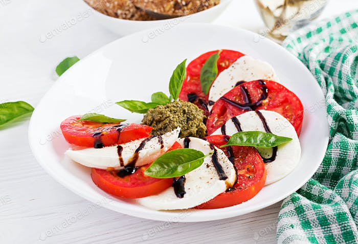 Traditional Italian Caprese Salad with mozzarella, tomato, basil and balsamic vinegar