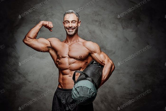 Pulido deportista posando en un estudio brillante con una bolsa de arena y mostrando los músculos