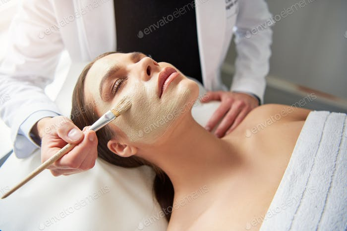 Unrecognizable cosmetologist applying mask on female face at cosmetology procedure