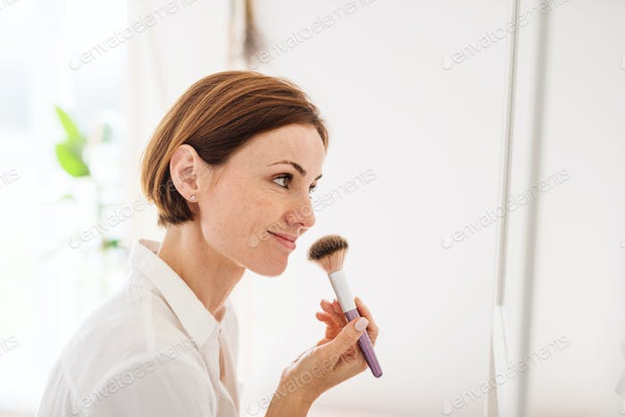 A young woman putting on a make-up in the morning in a bathroom.