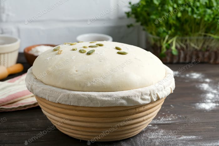 Homemade freshly prepared yeast dough in a basket for baking with pampkin seeds on a dark wooden