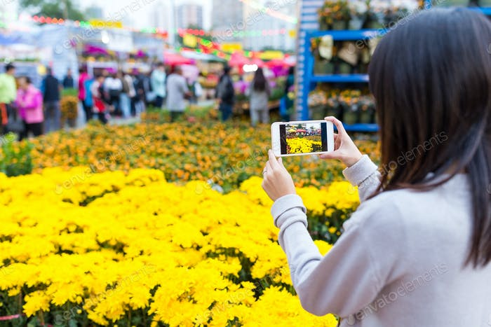 Woman taking photo with cellphone on Lunar new year flower market