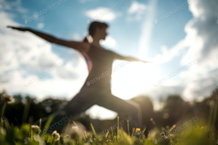 Sportlich fit kaukasische Frau tut Asana Virabhadrasana 2 Warrior Haltung in der Natur.