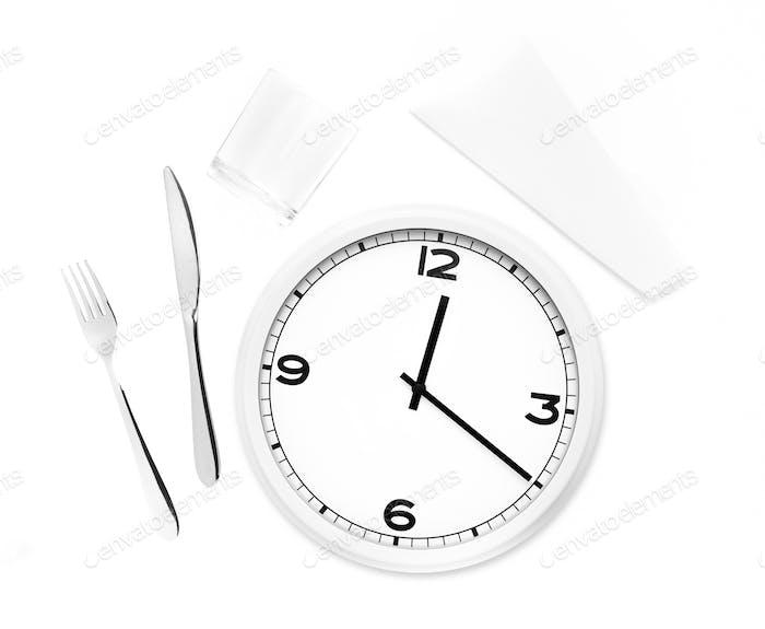 Fork, knife, glass, napkin and white round clock