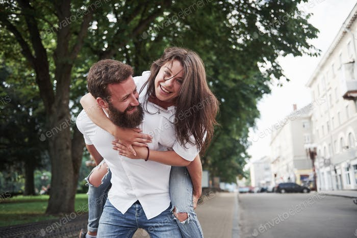 A young funny loving couple have fun on a sunny day.
