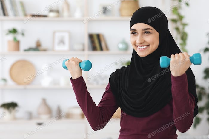 Home Workout. Strong young woman training with dumbbells in living room