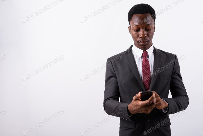 Young handsome African businessman using mobile phone against wh