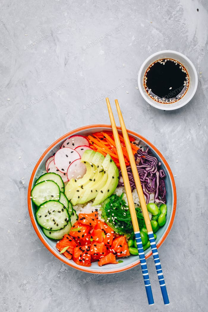 Salmon poke bowl with rice, avocado, seaweed, carrots, cucumber, radishes and edamame beans