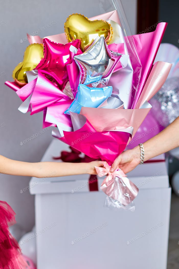 Congratulates the birthday girl and gives her a multicolored bouquet of ballons