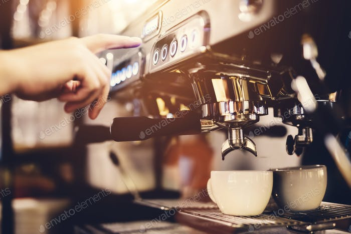 Hand pressing the button on a coffee machine. Coffee preparation.