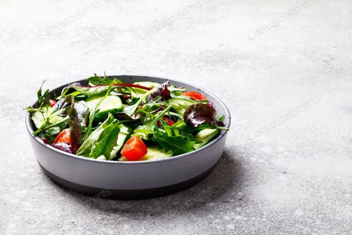Vegetable salad in a glass bowl with greens.Vegetarian Concept