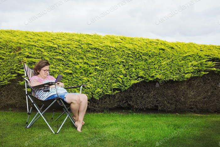 Frau sitzt in einem Campingstuhl an einem geschützten Ort an einer Hecke, mit einem digitalen Tablet.
