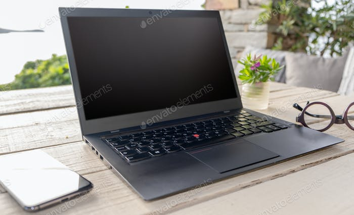 Blank screen laptop on the garden table, green nature background
