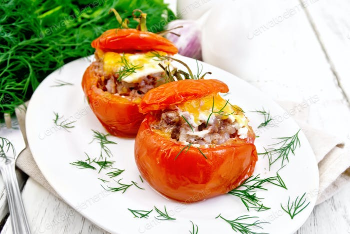 Tomatoes stuffed with meat and rice with dill in plate on board