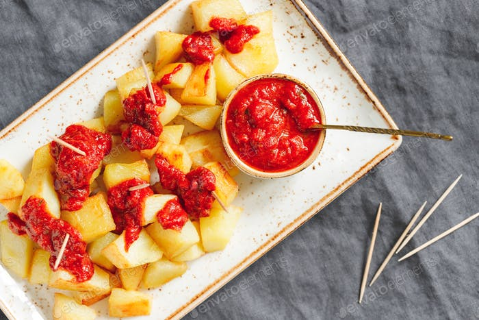 Top view on traditional tapas of Spanish cuisine Patatas Bravas