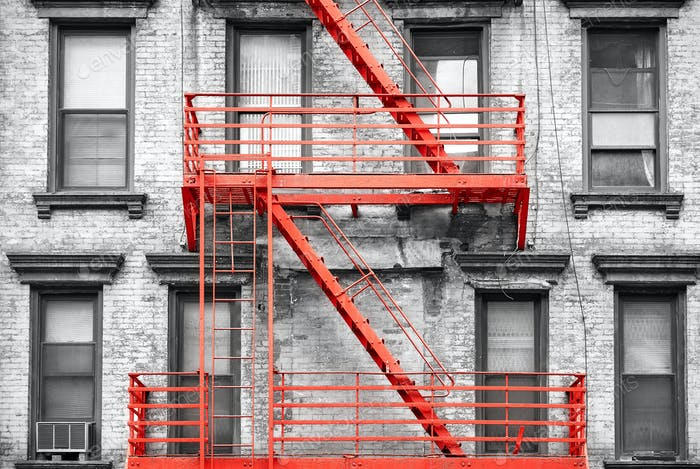 Red fire escape at black and white filtered residential building