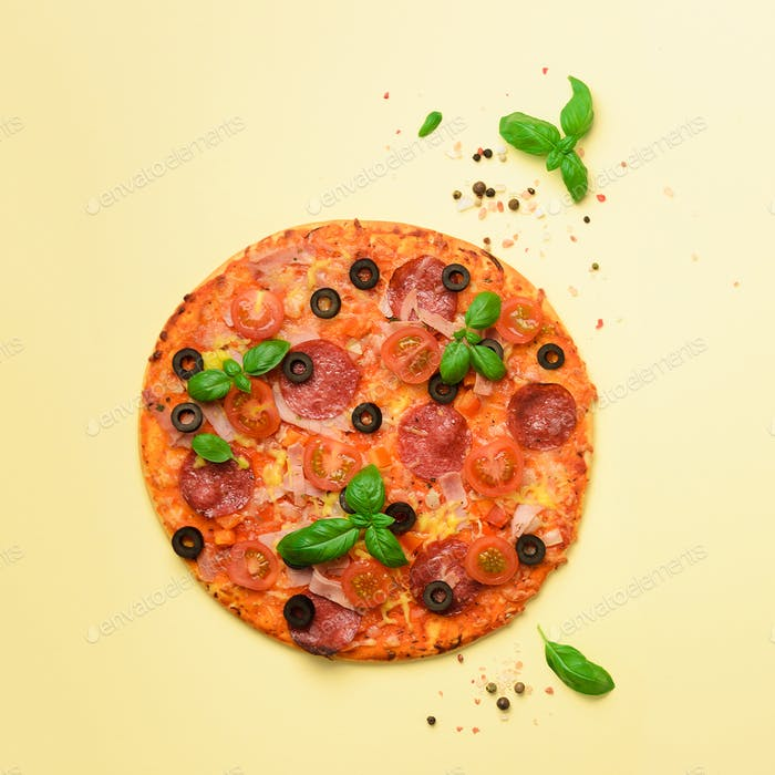 Delicious italian pizza, basil leaves, salt, pepper on yellow background with copyspace. Square crop