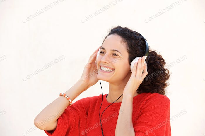 Close up beautiful young woman listening to music with headphone