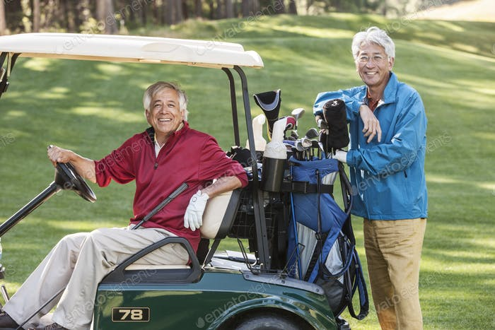 Two senior male golfing buddies and their golf cart and clubs.