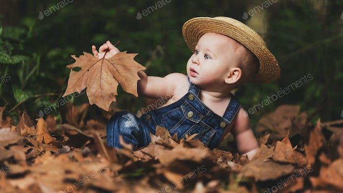Little boy playing in foliage