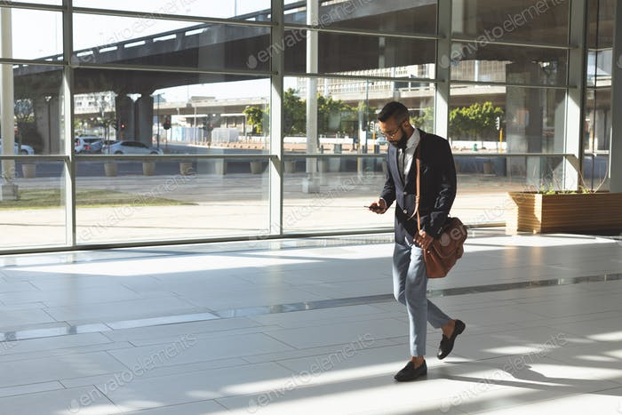 Side view of young businessman using mobile phone while walking in lobby office