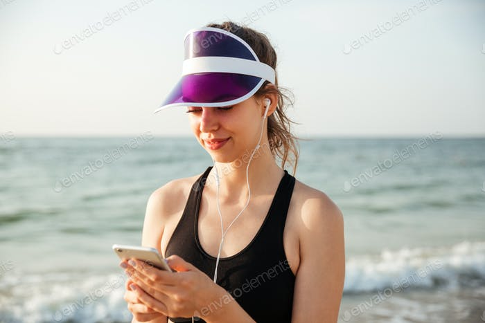 Fitness woman resting on beach listening to music with phone