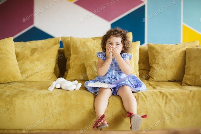 Niedliches kleines Mädchen mit dunklen lockigen Haaren in blauem Kleid mit Kind b