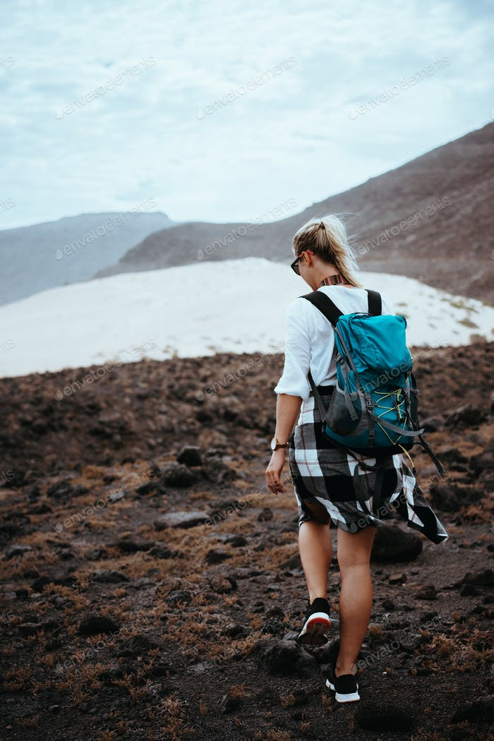 Woman hiker walking on barren rocky terrain among black volcanic boulders and white sand dunes. Sao