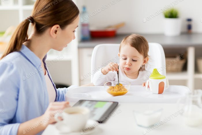 happy mother and baby having breakfast at home