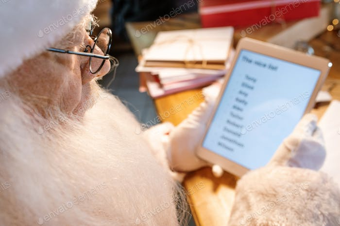 Mobile Santa looking through online nice list on touchscreen