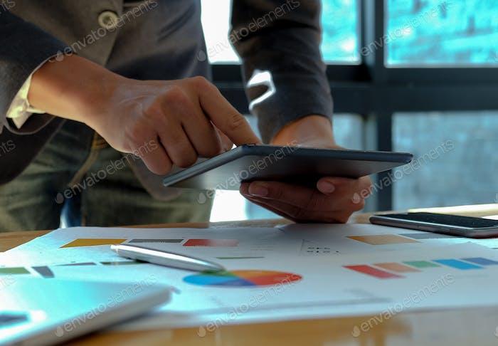 Handgeschäftsmann Arbeit auf Tablet im Büro mit Grafiken auf dem Schreibtisch