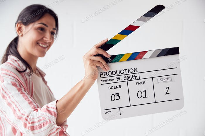 Female Videographer Holding Clapper Board On Video Film Production In White Studio