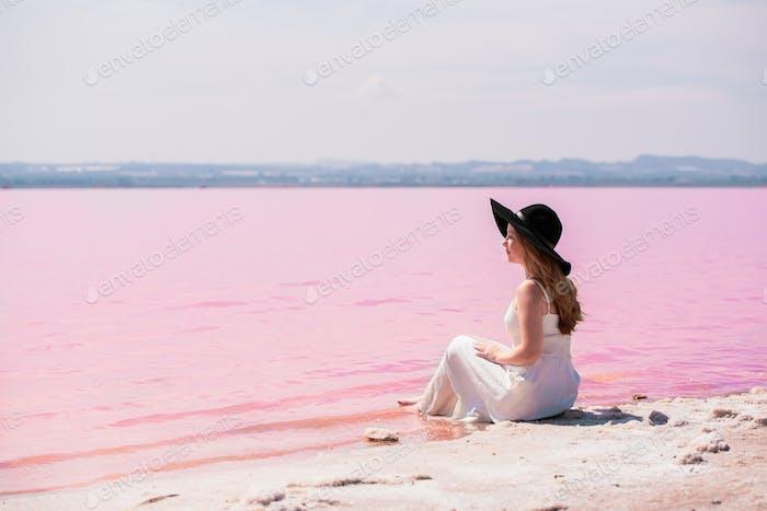 cute teenager woman wearing white dress sitting on an amazing pink lake