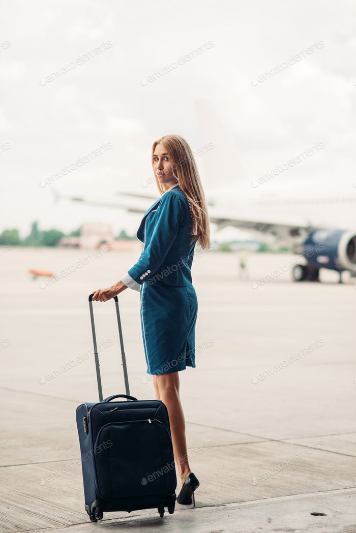 Young stewardess with suitcase on aircraft parking