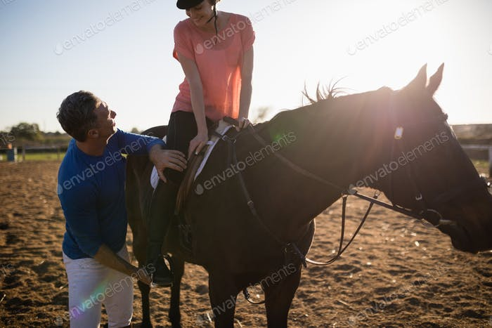 Male trainer adjusting young woman leg on stirrup