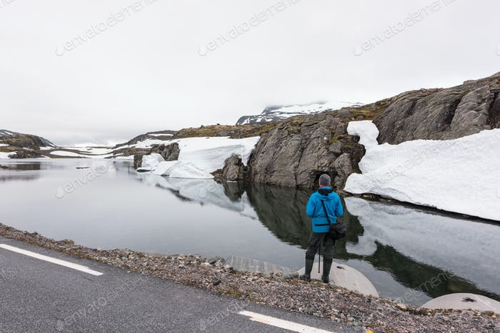 Photographer taking photo of typical norwegian landscape