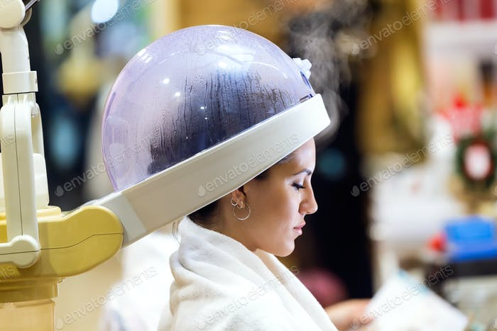 Beautiful young woman drying hair under machine in a beauty salo