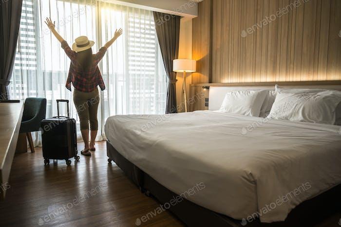 Happiness Asiatische Reisende Frau steht mit Gepäck im Schlafzimmer eines Hotels oder einer Herberge
