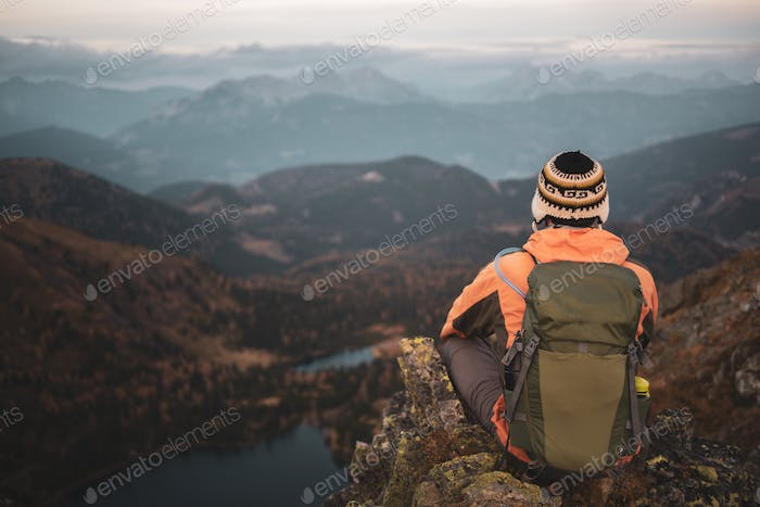 A man is sitting in the mountains
