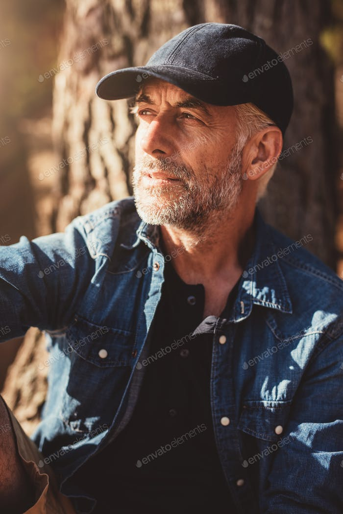 Mature man wearing cap sitting by a tree