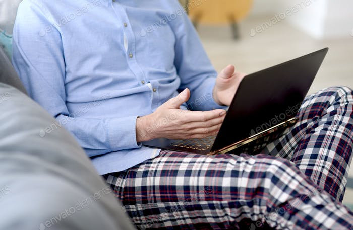 Unrecognizable person working at home on a laptop